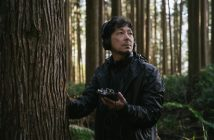 A man wearing a head set and standing in meddle of the forest