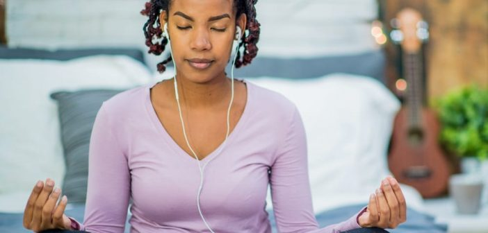 A woman doing meditation with music